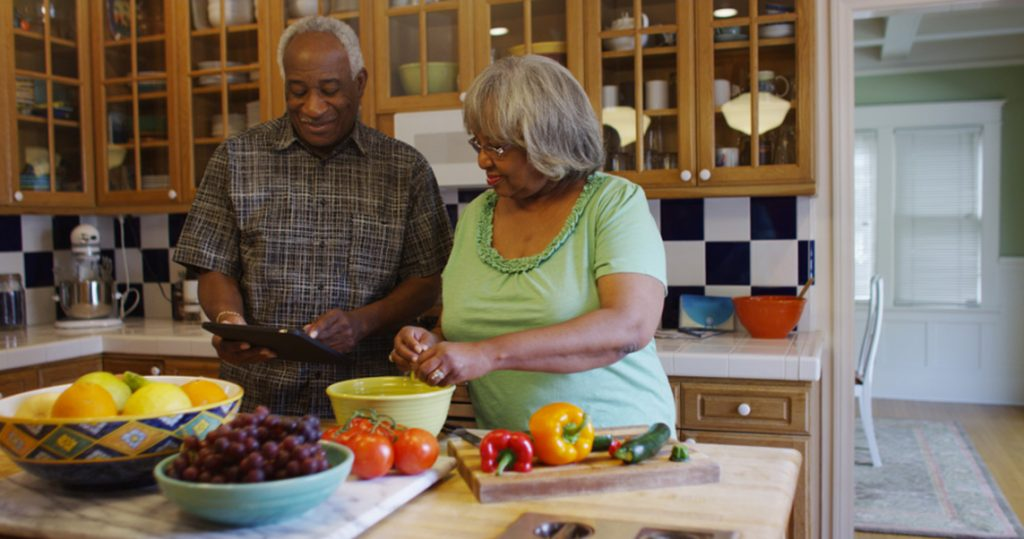 Retired couple in their kitchen checking their strong retirement savings on a tablet.