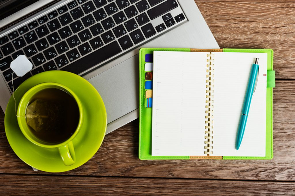 A day planner, laptop and cup of coffee on an attorney's desk.