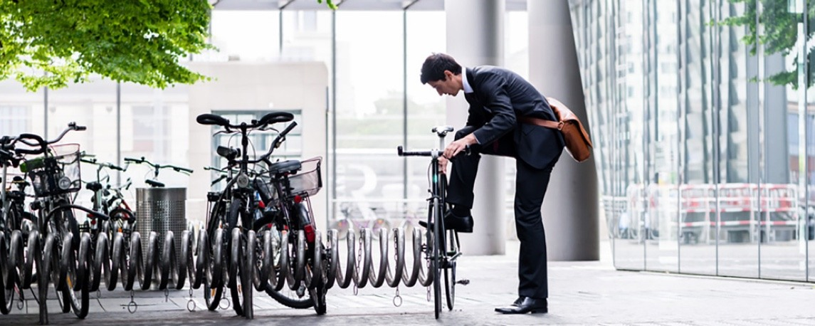 A buinessman takes his bicycle off the bike rack outside an office building